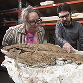 Photo of two people with a fossil