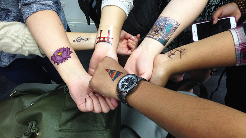 Six students show off their tattoo designs on their arms