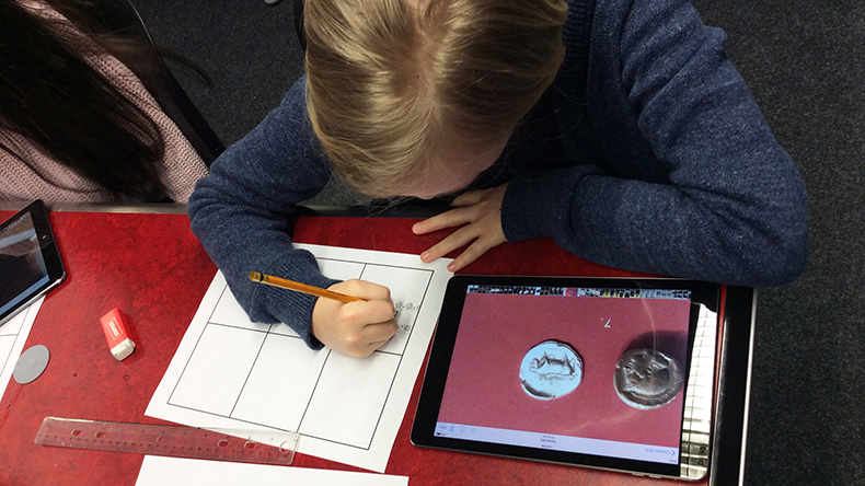 A student draws on a piece of paper with a coin image open on her iPad