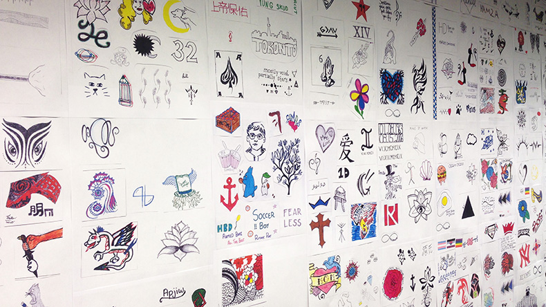 Hundreds of tattoo designs on white paper are posted on a wall