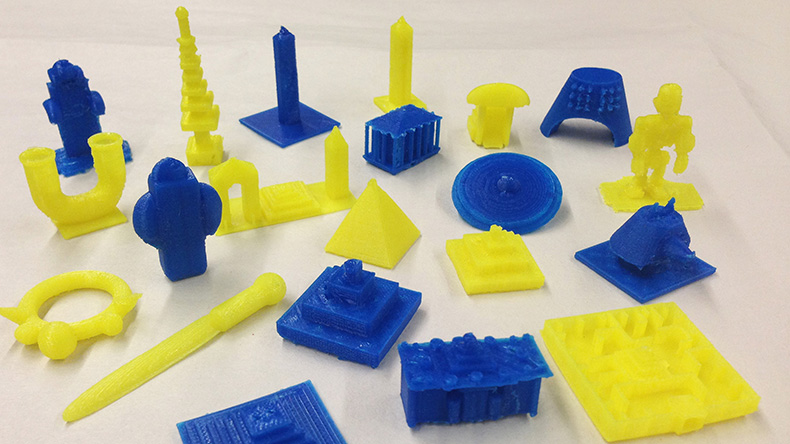 Twenty one blue and yellow 3D printed objects that include pyramids and obelisks