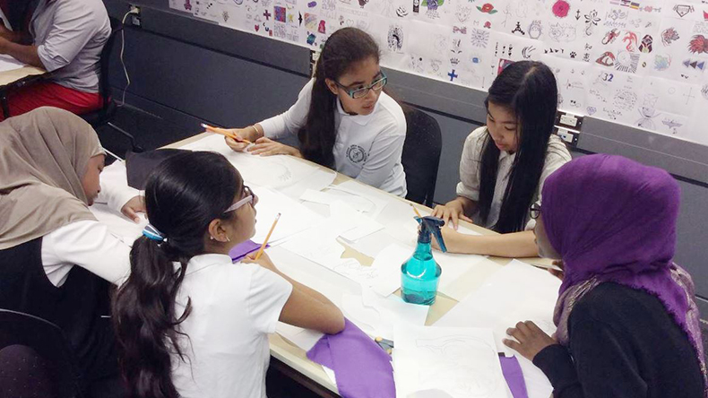 Five students around a table trace flag applique designs onto fusible interfacing fabric