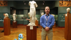 a man and a cartoon turtle stand in front of a statue of Aphrodite