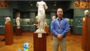 photo d'une homme et d'une tortue en dessin animé devant une statue d'Aphrodite