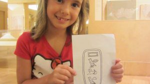 "a girl holds a paper showing the name ""Charlotte"" in hieroglyphs"