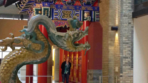 a woman stands next to a large digital dragon