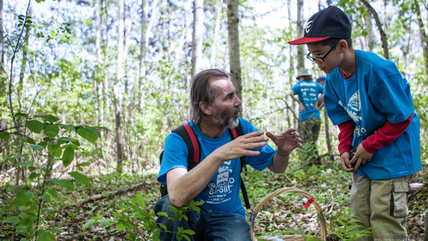 ROM scientist Jean-Marc Moncalvo gestures to a young boy to explain something about fungi during a guided bioblitz hike through the forest during the 2014 Ontario BioBlitz