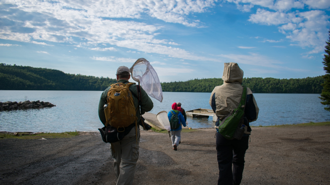 The insect team travels with nets in hand on a chilly morning towards the dock. Photo by Adil Darvesh
