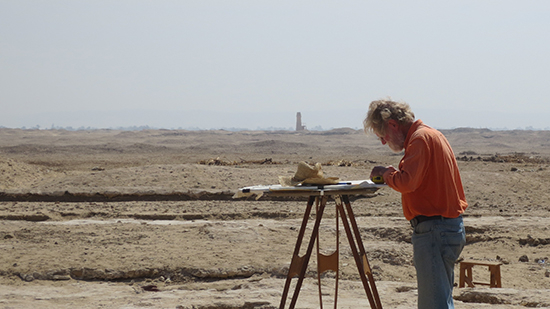 Man at work at an archaeological site with desert in background.