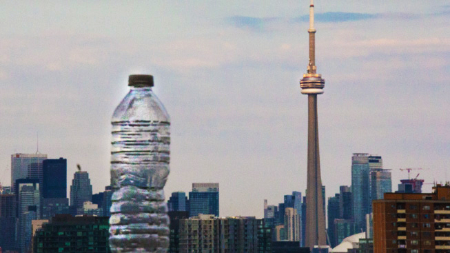 A photo of the skyline where a plastic water bottle stands next to Toronto's CN Tower. Photo credit: Cristina Bergman