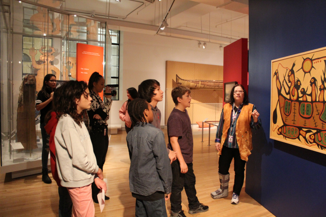 A teacher explaining a painting to students in the First Peoples Gallery