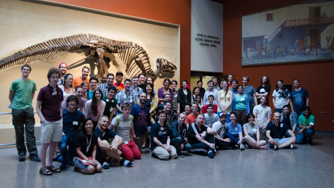 A group photo of all 2014 ROM Game Jam participants in front of a dinosaur skeleton