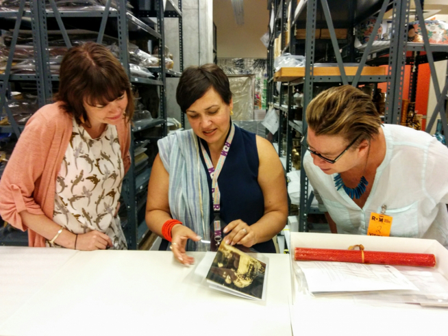 Photo of three people in collection storage looking at a photo