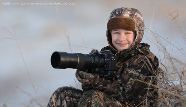 Ten-year-old wildlife photographer Josiah Launstein sits bundled up and ready to take the shot.