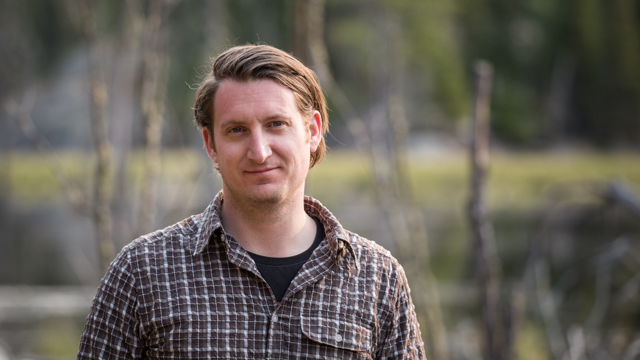 A portrait photo of Sebastian Kvist out in front of a swamp in the field in Minnesota, U.S.A. Photo by Vincent Luk
