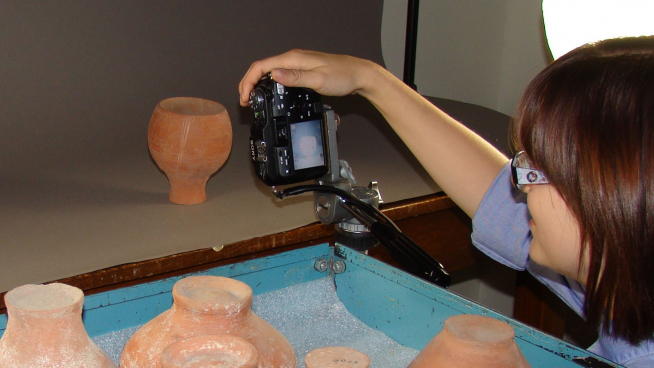 Woman photographing a clay pot, with a cart holding additional pots in the foreground