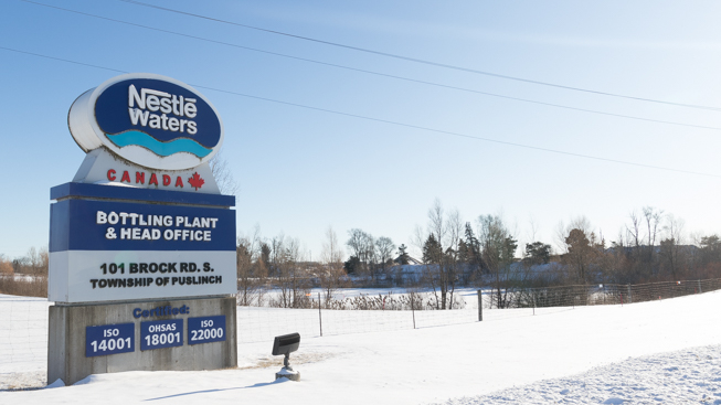 Large sign in snowy field reads: Nestlé Waters Canada bottling plant and head office 101 Brock Rd.S., Township of Puslinch