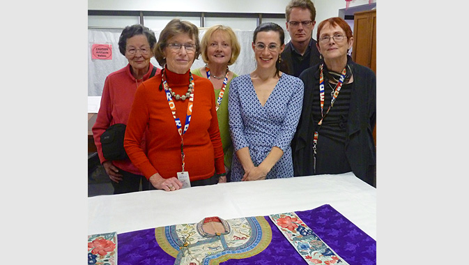 Rachel Silberstein, the Veronika Gervers Research Fellow in 2012, shows Chinese embroidery in the ROM's collection to Patricia Harris and other FTC executives and donors
