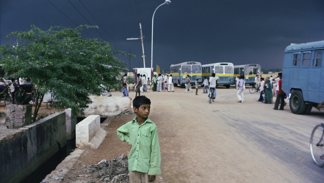 Boy waiting in front of bus station