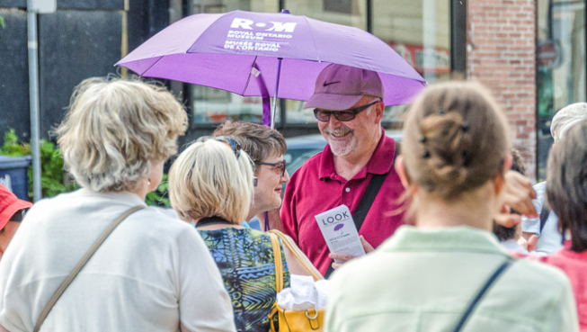 "Photo of a crowd of people surrounding a man with a purple umbrella that says ""Royal Ontario Museum"""
