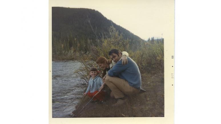 Homme, femme et enfant accroupis près d'un lac