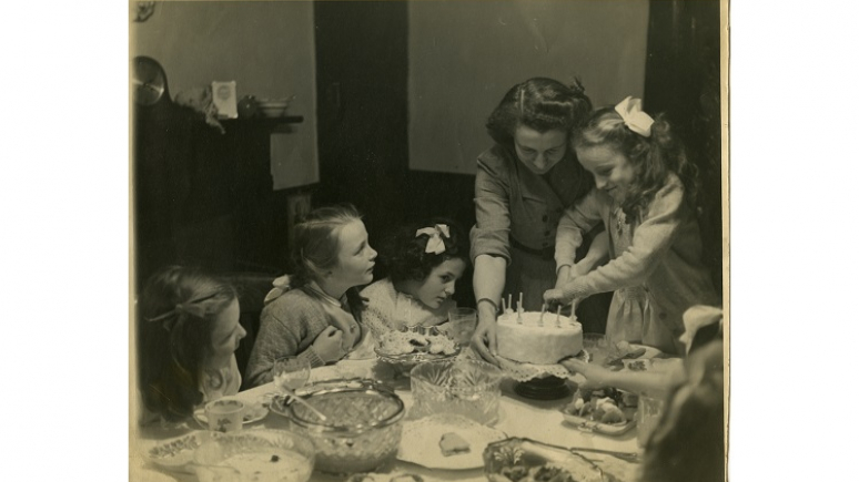 Four children and a woman cutting a birthday cake.