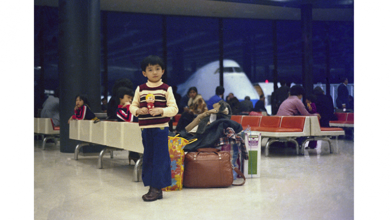 Boy standing in an airport with a plane in the background.