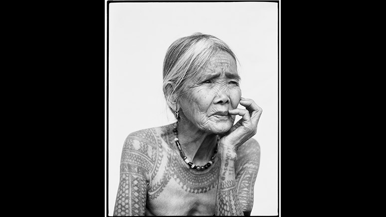 Portrait of an elderly woman with tattoos.