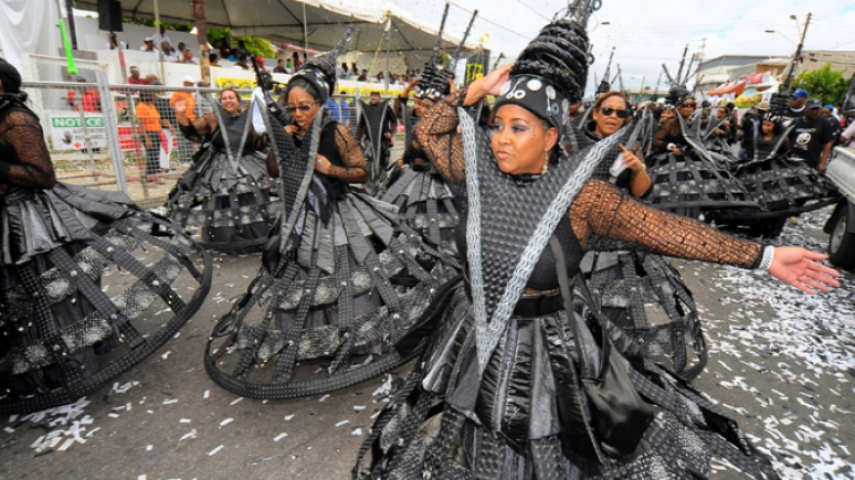 Women wearing grey costumes walking in parade.