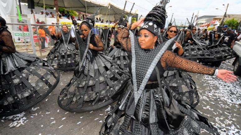 Women wearing grey costumes walking in parade.