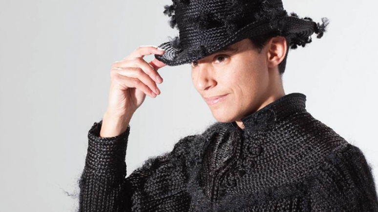 Photograph of artist Karin Jones wearing the mournning dress and a top hat made of synthetic hair.