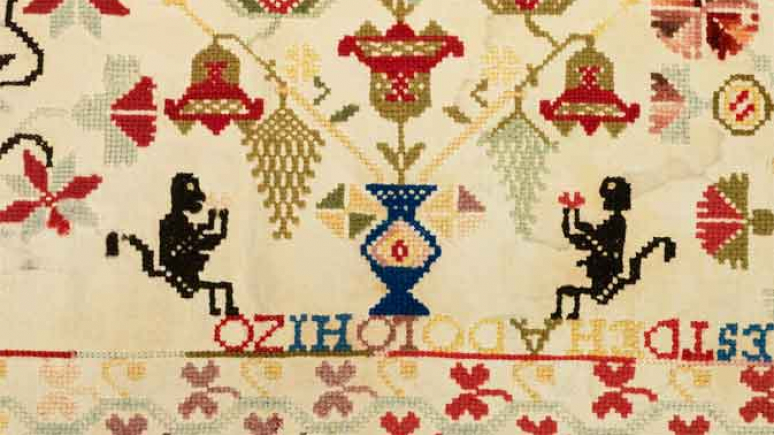 Detail of a sampler embroidered in cross-stitch showing two monkeys flank an urn of flowers.