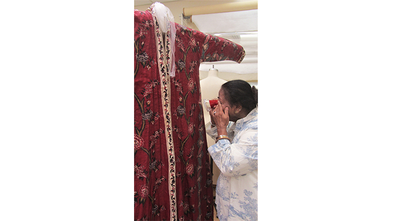 Jagada examining the patterns and colors of an eighteenth-century man's dressing gown or banyan, Textile Study Room, ROM, October 2018.