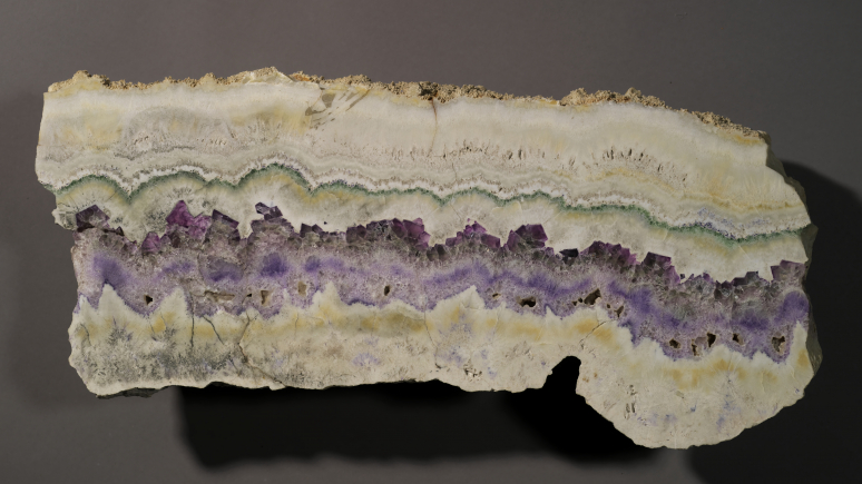 The specimen is grays and purples with lines of each colour.