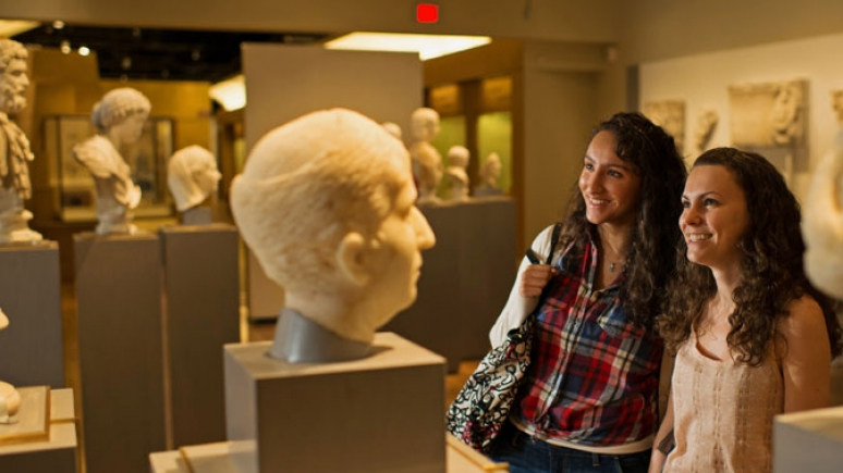 Women look at the Greek and Roman busts featured in the Eaton Gallery of Rome.