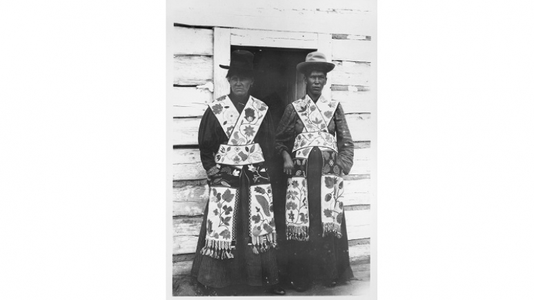 Two Anishinaabeg women wearing hats and friendship bags.