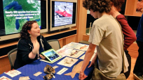 Visitors gather around a table with touchable natural history specimens