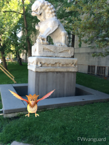 a cartoon bird in front of a chinese lion statue