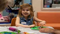 Photo of a girl at Sick Kids doing a dinosaur craft. Photo credit Mark Bernards3