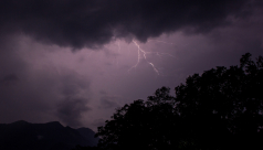 A bolt of lightning streaks across a purple sky over the mountains and rainforests of Sri Lanka