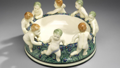 A colourful earthenware bowl with figures of putti dancing around outter rim.