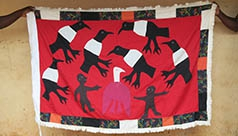 People holding up a handmade flag depicting birds.