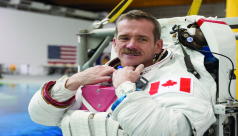 A photograph of a man in an astronaut suit without a helmet