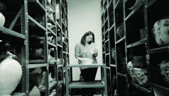 A black and white photograph of a woman standing on a step ladder surrounded by artifacts on shelves