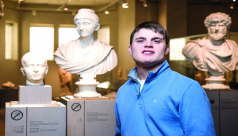 A photograph of a young man in a blue sweater standing in front of three Roman busts.
