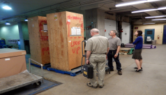 Inside the shipping room, inspecting a wooden crate