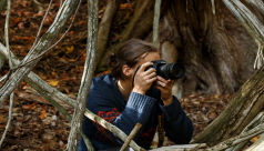 A woman crouches in the woods, her camera raised to her face, ready to take a photo.