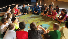 In this photo, taken in 2014, Canadian Space Agency (CSA) astronaut David Saint-Jacques unveiled the Canada from Space Giant Floor Map to a group of students in Ottawa. © Canadian Space Agency.