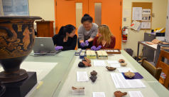 The ROM's Kay Sunahara examining Roman coins with interns Menghan Yan & Clare Schwartzberg, surrounded by artifacts being prepared for the upcoming Ancient Greece & Rome Weekend exhibit