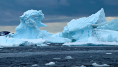 A photo of massive ice bergs on the ocean in front of a stormy sky. Photo by Jeff Dickie